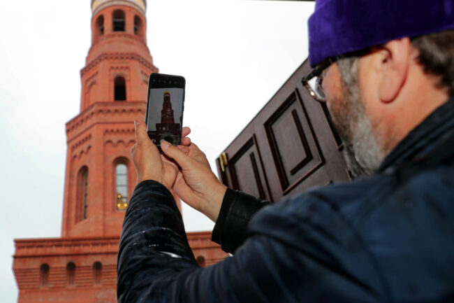 священник, мобильный телефон, фотография на смартфон, Исидоровская колокольня Воскресенского Новодевичьего монастыря